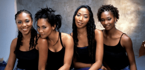 A row of four women with black t-shirts and different hairstyles