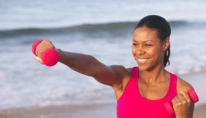 african american woman on the beach with a weight in hand