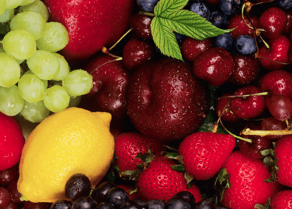 A variety of different types of fruits, including grapes, strawberries and plums