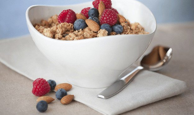 A bowl of cereal with nuts, raspberries and blueberries