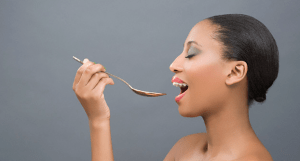 A woman holding a spoon up to her mouth