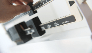 A hand adjusting a weight scale