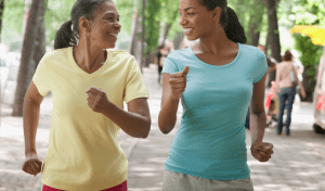 A mother and her adult daughter speed walking together in a park