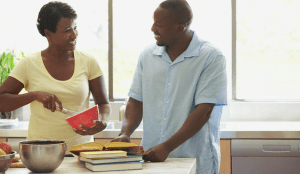 A couple cooking with a cookbook