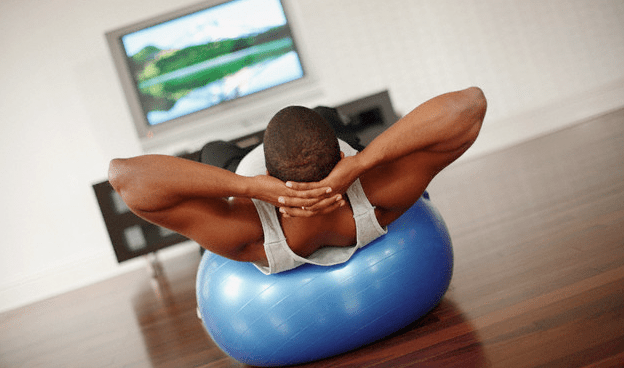 A man watching tv while doing crunches on a blue fitness ball