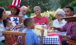 A large family sitting at a picnic table for a July 4th barbecue