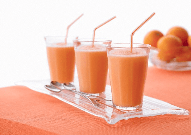 Three orange smoothies on a glass tray