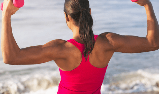 A woman in a red top lifting red dumbbells at the beach