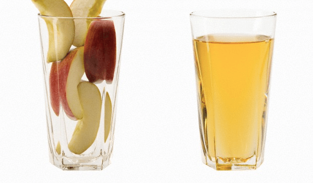 A glass filled with apple juice next to a glass filled with apple slices
