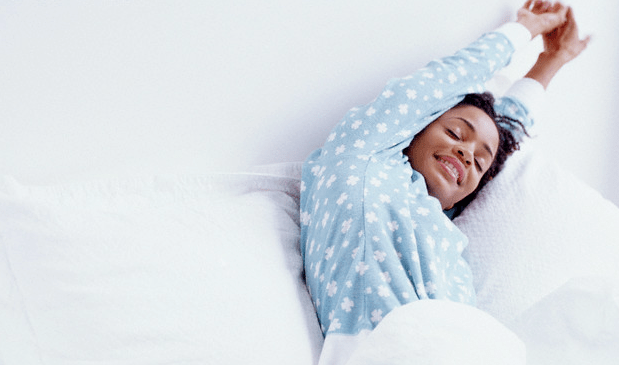 A smiling woman wearing blue pajamas stretching in her bed