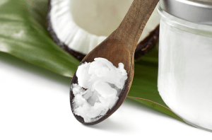 A wooden spoon with coconut oil, beside a jar of coconut oil and a raw coconut half