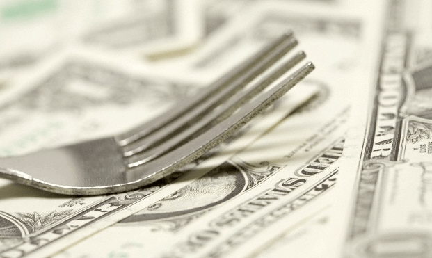 Dollar bills with a fork sitting on top