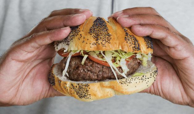 A man's hands holding a burger