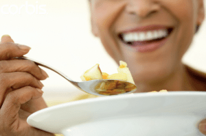 A smiling woman eating from a bowl