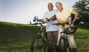 A smiling, older couple standing together with their bikes