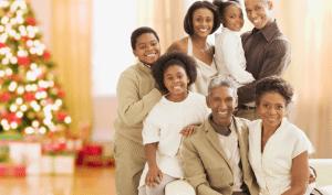 A multi-generational family posing near a Christmas tree