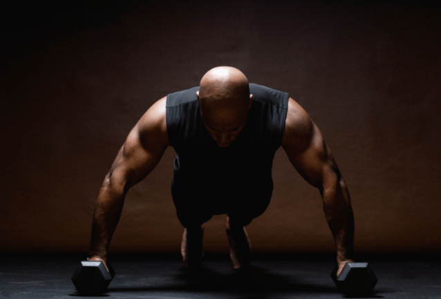 A man doing push-ups with weights