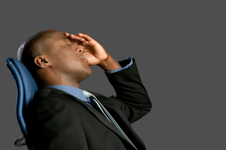 Businessman leaning back in chair with hand on forehead