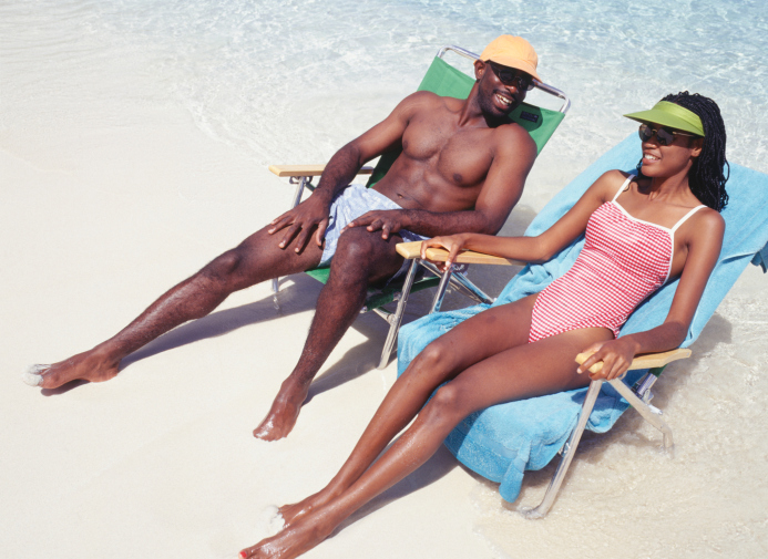 Man and woman sunbathing in deckchairs on beach