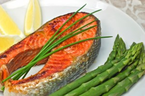 salmon steak dinner with asparagus and a lemon wedge