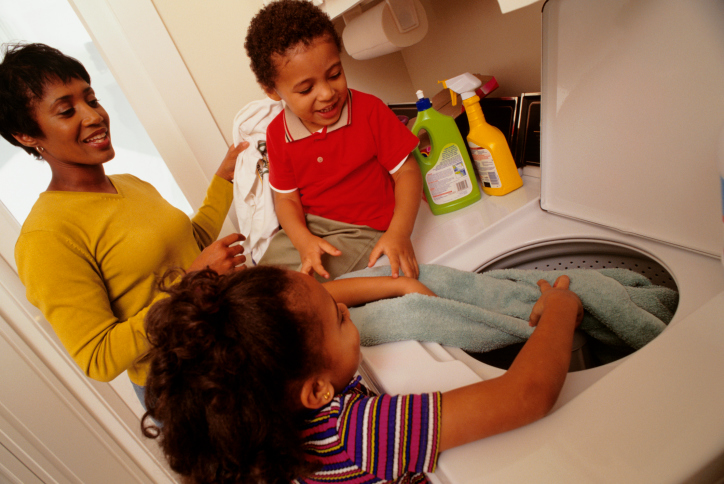 Mother with children putting laundry into washing machine