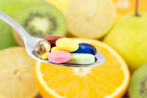 spoonful of different pills, different fruits in background