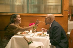 african american woman feeding african american man in a restaurant
