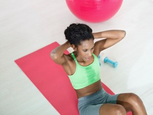 african american woman doing crunches in the gym