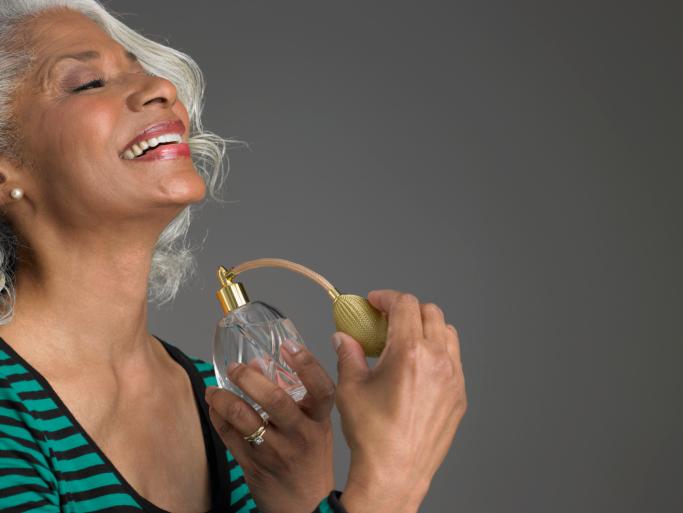 older woman spraying perfume