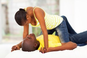 african american couple play fighting in bed