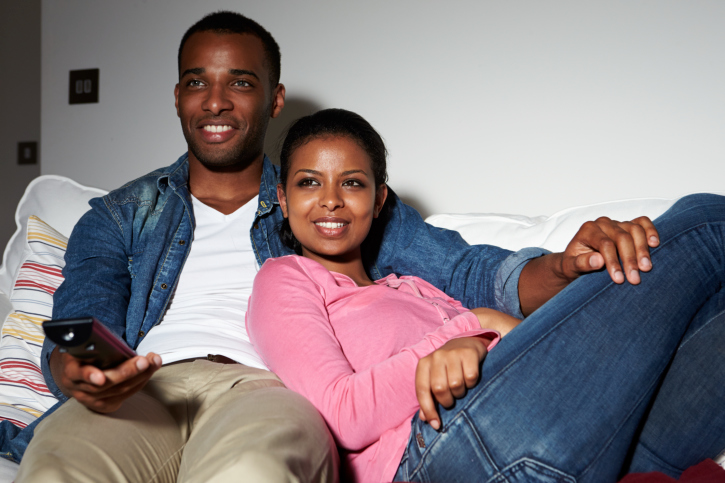 Couple Sitting On Sofa Watching TV Together