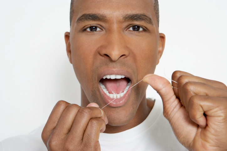 African American Black man flossing teeth