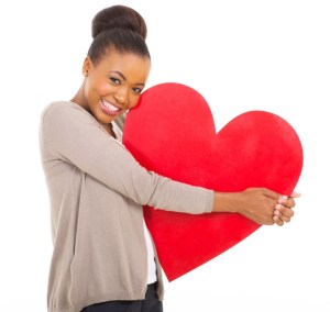 woman hugging large red heart
