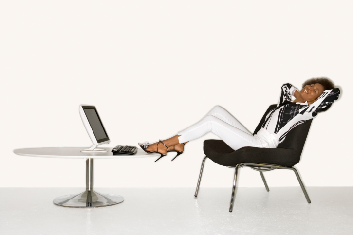 Reclining woman with feet up by computer