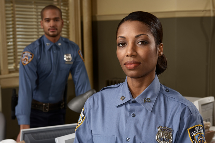 Young policewoman and young policeman in office, portrait