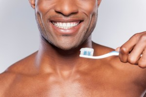 african american man smiling while holding a toothbrush
