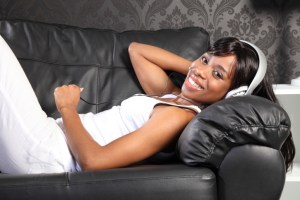 african american woman laying on couch listening to music