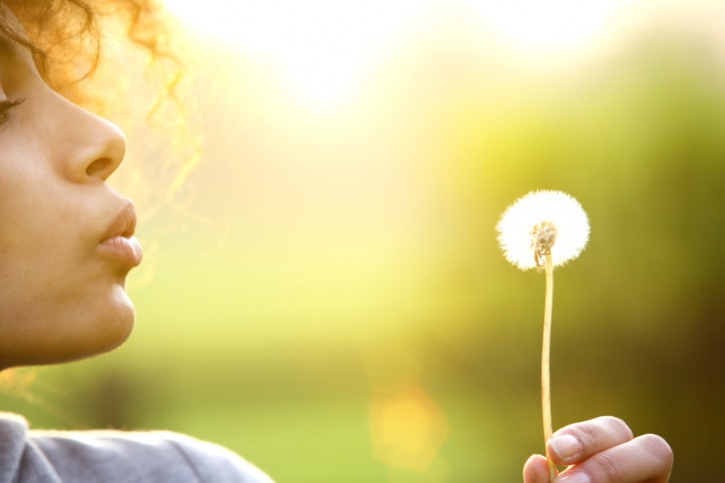 Young woman blowing dandelion flower outdoors