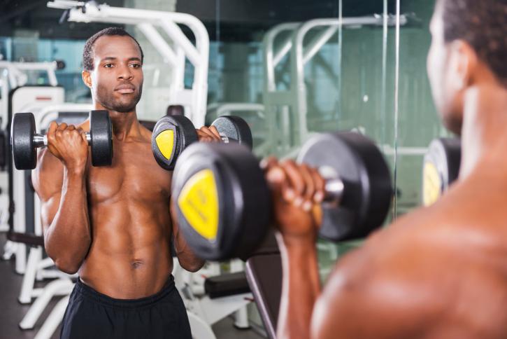 Man lifting weights mirror