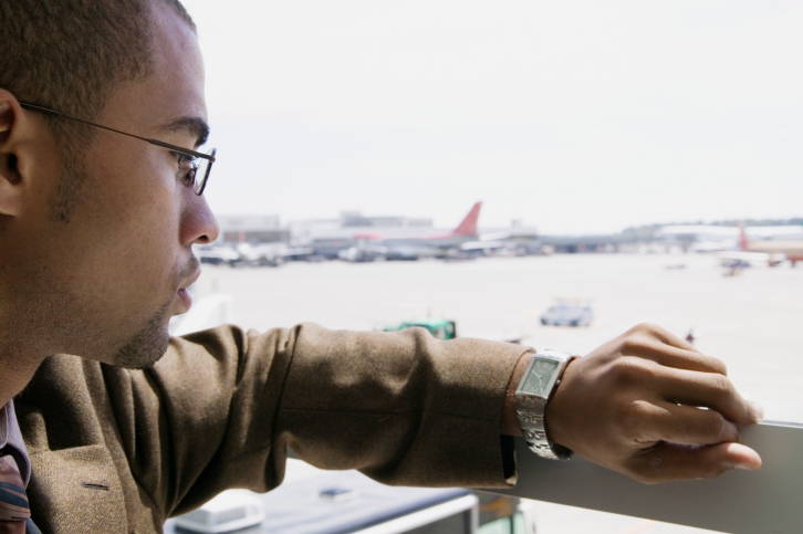 businessman looking at watch airport