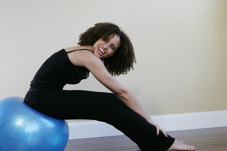 Woman sitting on a exercise ball, smiling