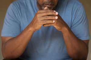 depressed man, hands folded