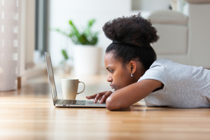 African American Black woman sad serious using a laptop in her living room