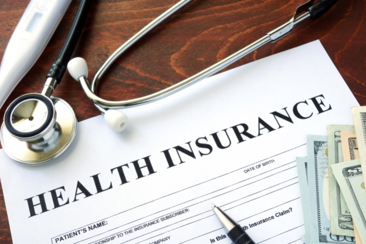 Health insurance form and dollars on the table