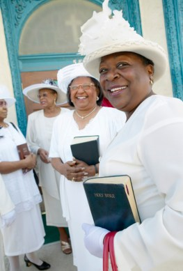 Congregation of Women Dressed in White Clothing Standing Outside a Church