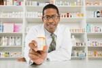 African American man pharmacist holding prescription bottle