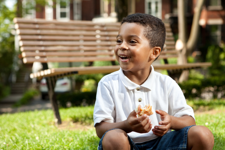 little boy eating in the park