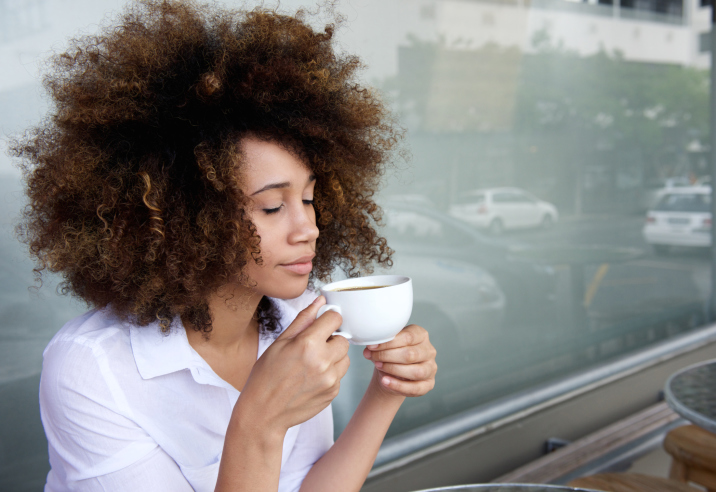 African American woman inhaling cup of coffee tea