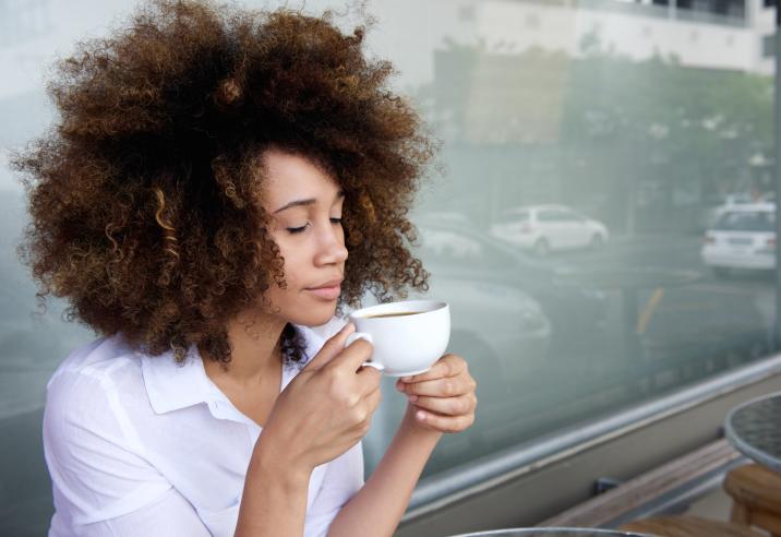 African American woman inhaling cup of coffee tea