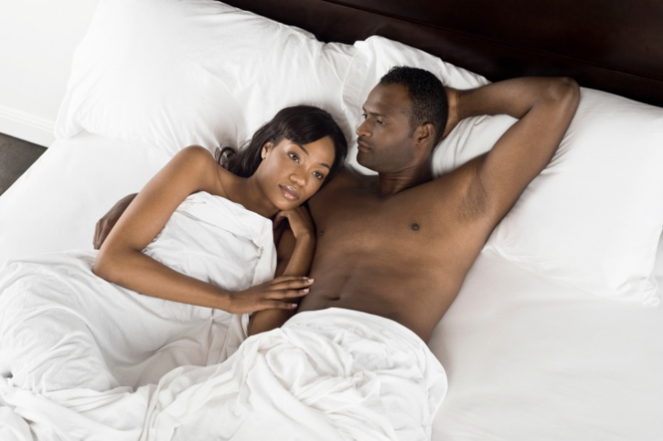 African American man with arm around woman laying bed